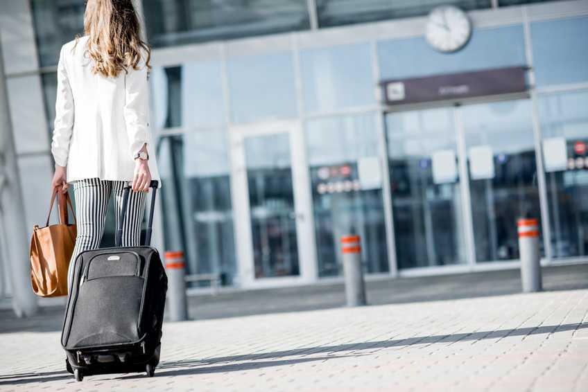 Forretningskvinne på vei inn på flyplass.