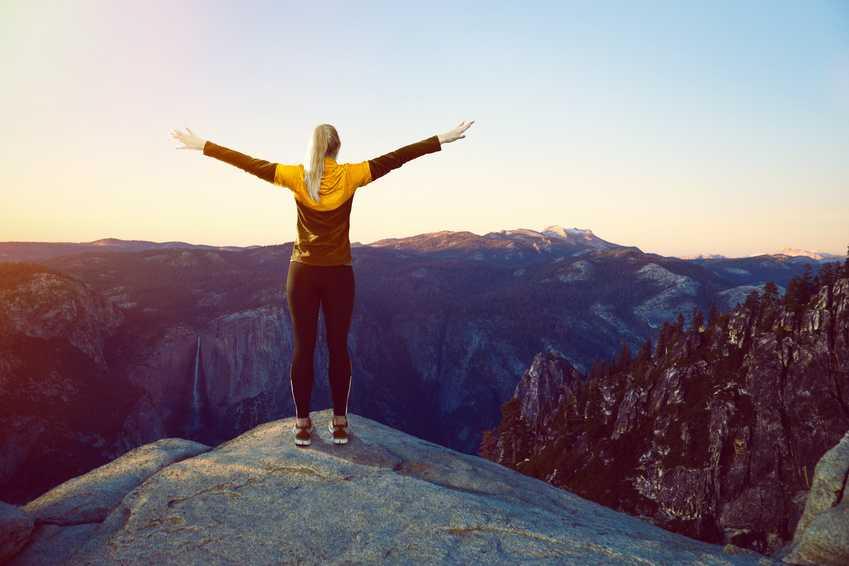 Ung kvinner ser ut over et imponerende fjell-landskap