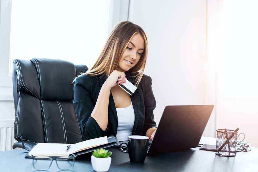 Forretningskvinne holder kredittkort foran bærbar pc