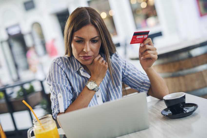Ung kvinne holder opp et kredittkort mens hun ser på en pc-skjerm