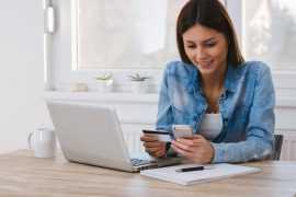 Ung kvinne studerer telefonen sin med kredittkort i hånden