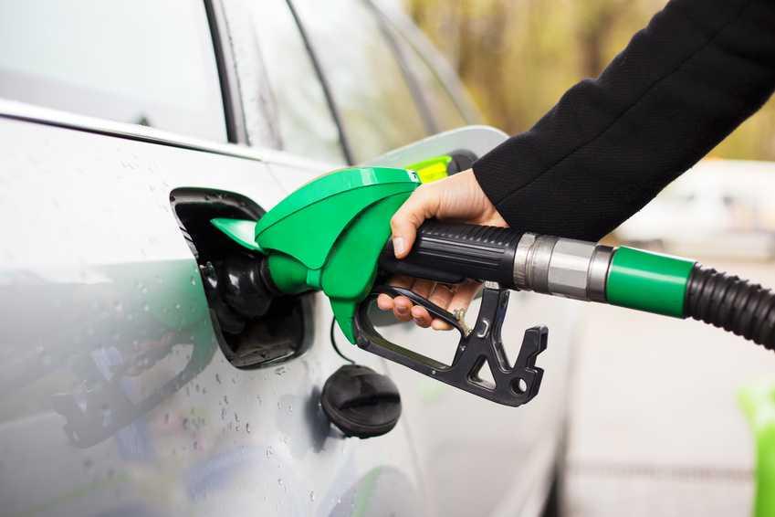 Kvinne fyller besintanken på bensinstasjon.